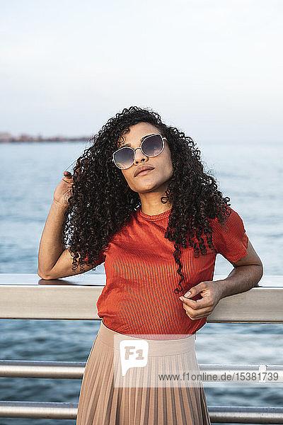 Schöne Frau  Sonnenbrille tragend  an der Reling am Meer lehnend Schöne Frau, Sonnenbrille tragend, an der Reling am Meer lehnend
