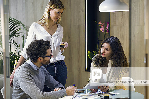 Three business people having a meeting in modern office