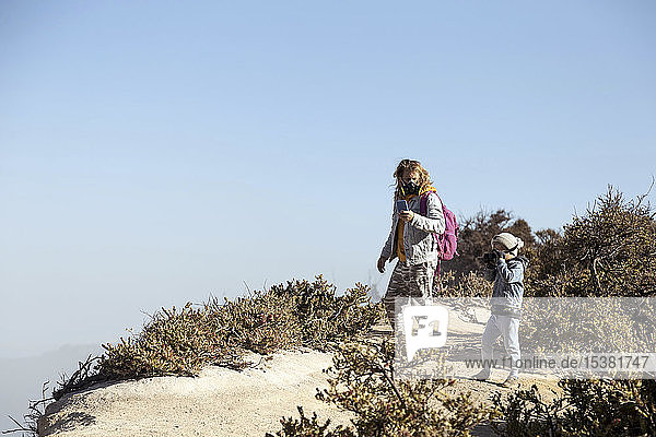 Father and son with respirator masks standing at the edge of volcano Ijen  Java  Indonesia