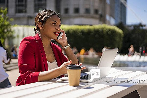 Geschäftsfrau am Telefon mit Laptop und Kaffee  um nach draußen zu gehen  London  Großbritannien