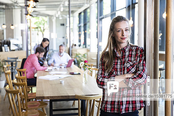 Porträt einer ungezwungenen Geschäftsfrau in einem Cafe mit Kollegen  die im Hintergrund eine Besprechung abhalten