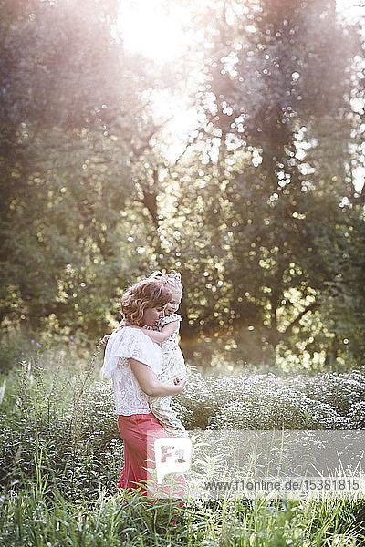 Mutter trägt ihre Tochter auf einer Blumenwiese