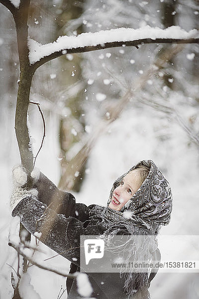 Portrait of smiling little girl shaking tree in winter forest
