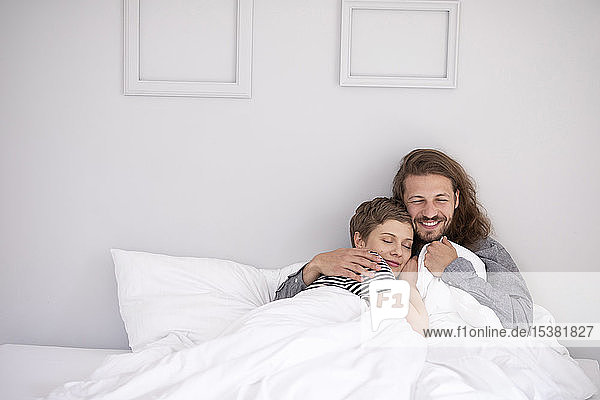 Glückliches junges Paar kuschelt zu Hause im Bett