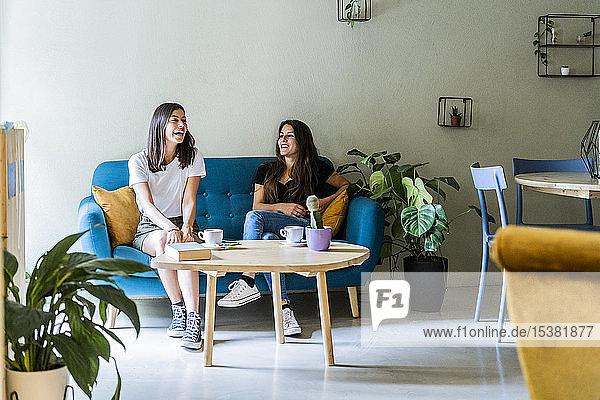 Zwei glückliche junge Freundinnen sitzen auf einer Couch in einem Cafe