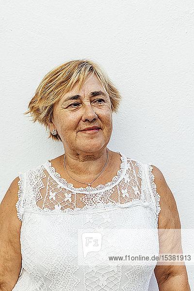 Porträt einer älteren Frau mit weißem Wandhintergrund