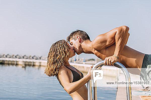 Junges Paar küsst sich auf einer Mole am Meer