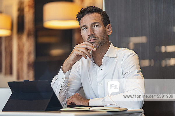 Businessman with tablet and notebook in a cafe thinking
