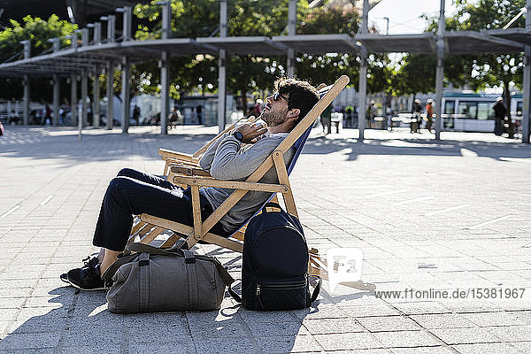 Man relaxing in deckchair on urban square