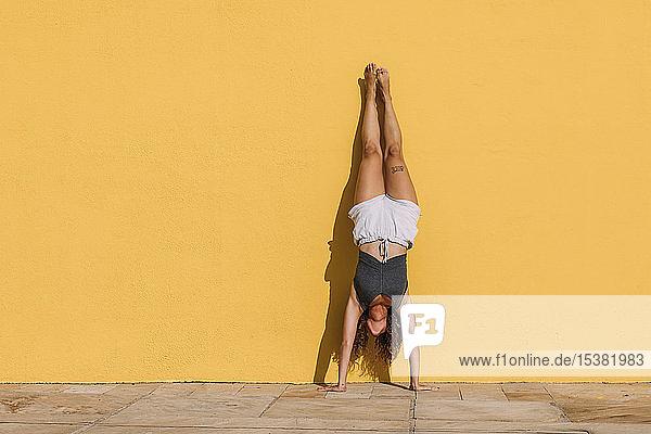 Junge Frau macht einen Handstand vor einer gelben Wand