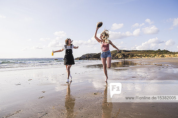 Two girlfriends having fun  running and jumping on the beach