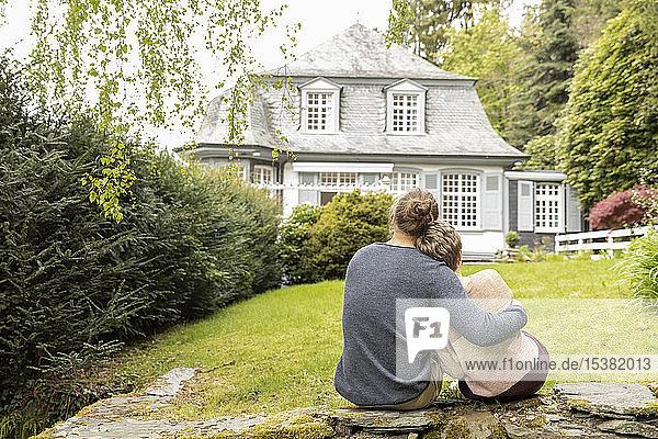 Rückansicht eines Paares  das auf einer Mauer im Garten sitzt