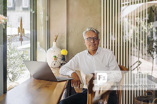 Porträt eines hochrangigen Geschäftsmannes mit Laptop in einem Cafe