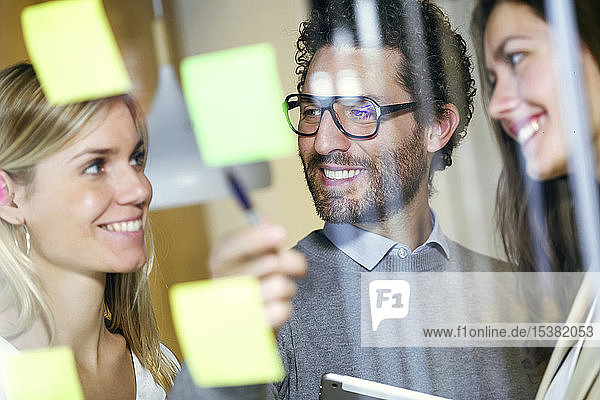 Three smiling business people brainstorming together with sticky notes on a glass wall