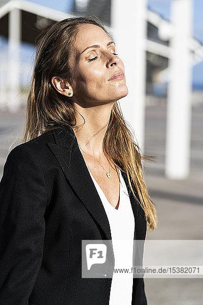 Geschäftsfrau steht im Freien und genießt den Sonnenschein