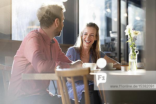 Lachende Frau und lachender Mann unterhalten sich am Tisch in einem Cafe