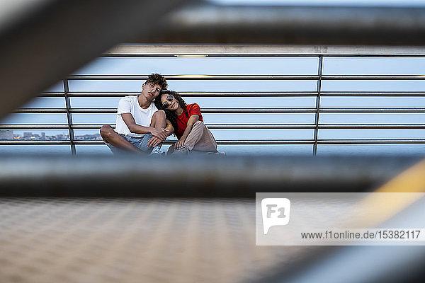 Junges Paar auf der Brücke am Meer sitzend Junges Paar auf der Brücke am Meer sitzend