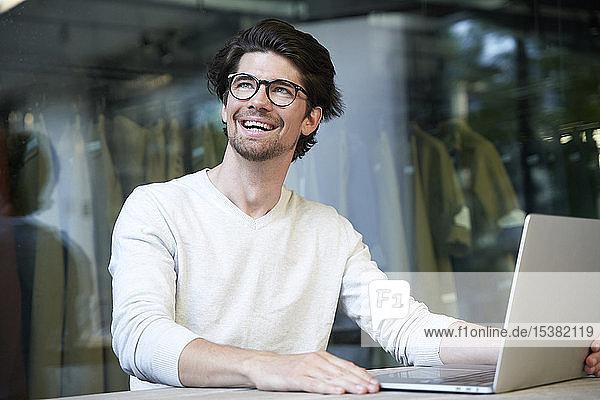 Glücklicher Geschäftsmann mit Laptop in der Stadt