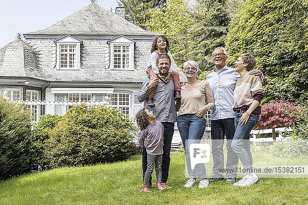 Glückliche Großfamilie steht im Garten ihres Hauses