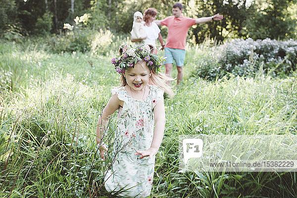 Glückliches kleines Mädchen mit Blumenkranz  das in der Natur vor seinen Eltern wegläuft Glückliches kleines Mädchen mit Blumenkranz, das in der Natur vor seinen Eltern wegläuft