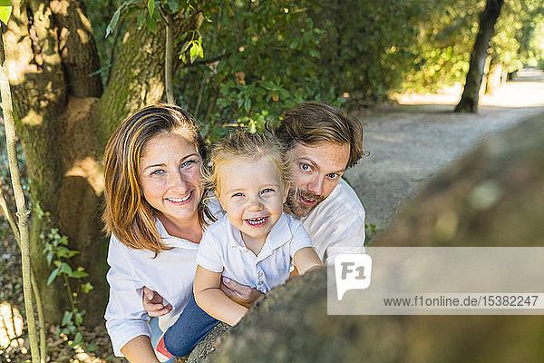 Porträt von Eltern mit kleiner Tochter in einem Park