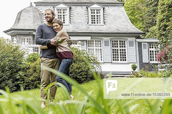 Glückliches junges Paar umarmt sich im Garten ihres Hauses