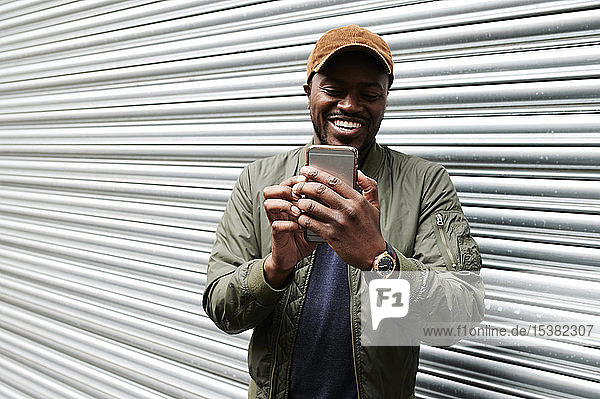 Portrait of laughing man taking selfie with smartphone