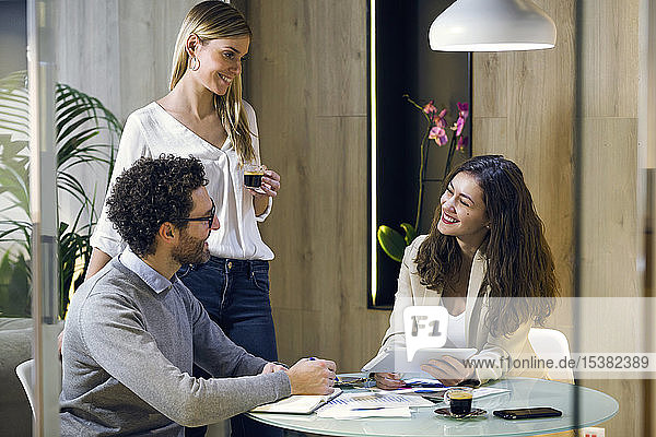 Three happy business people having a meeting in modern office