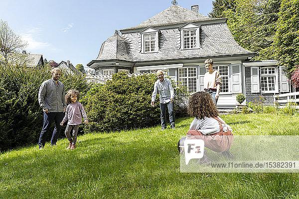 Glückliche Grossfamilie spielt Fussball im Garten