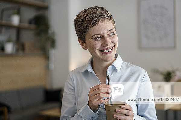 Glückliche Geschäftsfrau in einem Cafe mit einer Tasse in der Hand