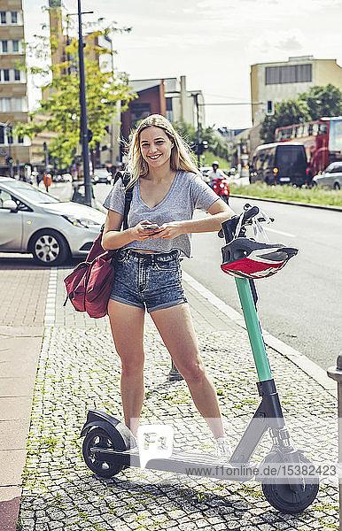 Porträt einer lächelnden jungen Frau mit E-Scooter in der Stadt  Berlin  Deutschland