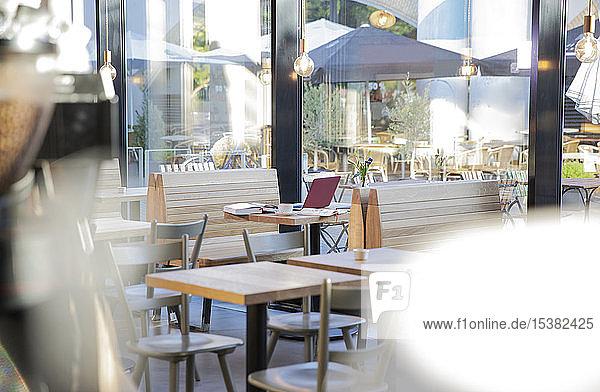 Laptop und Bücher auf dem Tisch eines modernen Cafés
