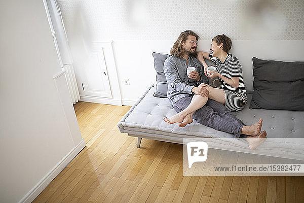 Glückliches junges Paar im Pyjama auf der Schlafcouch zu Hause