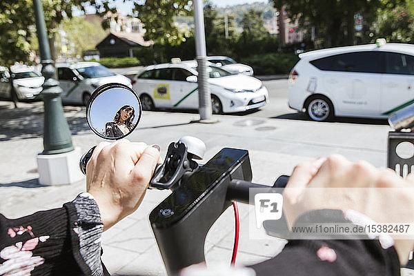 Junge Frau mit E-Scooter in der Stadt  Rückspiegel