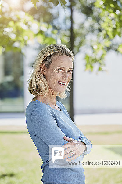 Portrait of smiling blond woman in a park