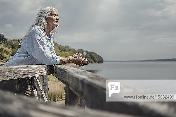 Senior woman standing on bridge  relaxing with eyes closed