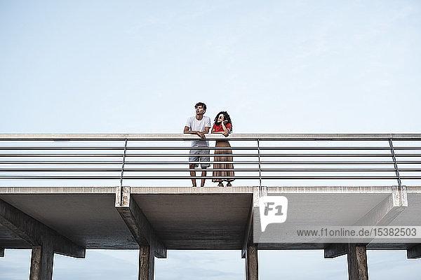 Junges Paar steht auf der Brücke und schaut auf die Aussicht Junges Paar steht auf der Brücke und schaut auf die Aussicht
