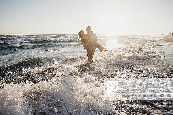Glücklicher junger Mann mit Freundin bei Sonnenuntergang am Meeresufer