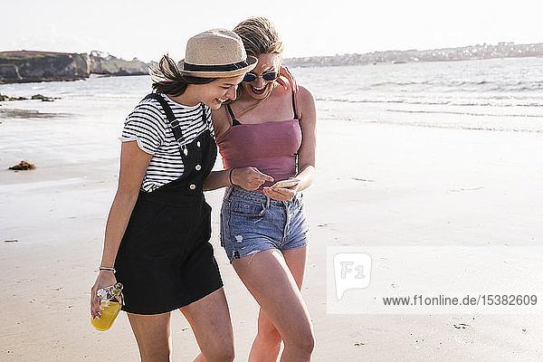 Zwei Freundinnen amüsieren sich  gehen am Strand spazieren  nehmen selbst ein Smartphone