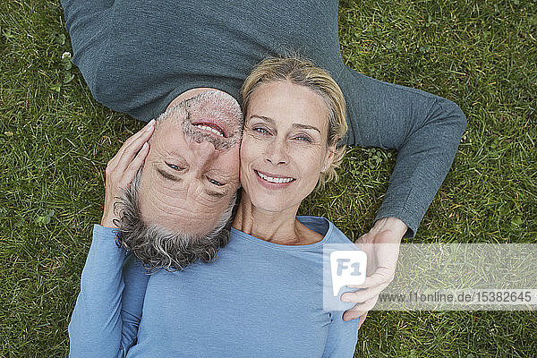 Top view of happy mature couple lying in grass