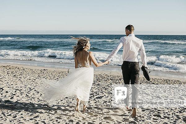 Rückansicht von Braut und Bräutigam beim Laufen am Strand