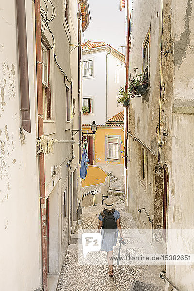 Tourist walking in an alley in the old town of Coimbra,  Portugal