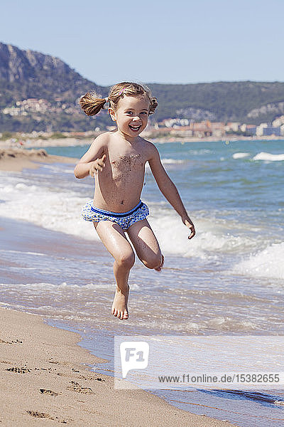 Portrait of happy little girl jumping in the air on the beach  Girona  Spain