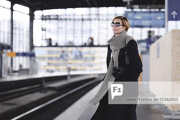 Reife Frau mit Kamera in schwarzem Mantel und großem Wollschal wartet am Bahnsteig
