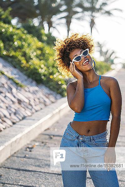Porträt einer lachenden jungen Frau mit Sonnenbrille