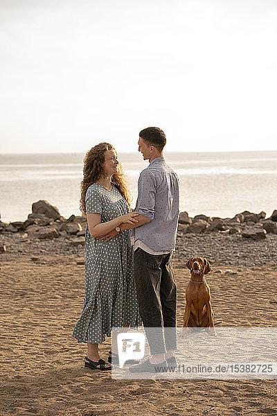 Junges Paar mit Hund am Strand