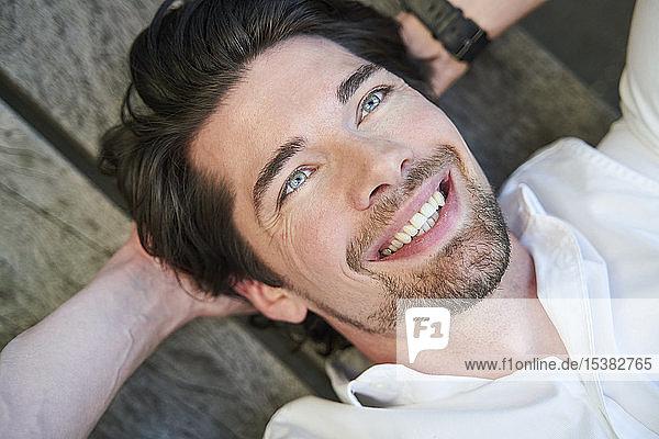 Porträt eines glücklichen Geschäftsmannes auf einer Bank liegend