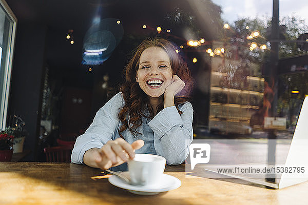 Portrait of happy redheaded woman with laptop in a cafe