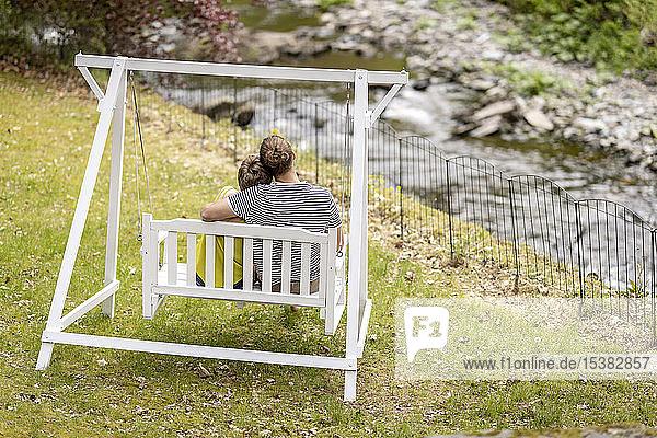 Rückansicht eines lächelnden Sitzens auf einer Baldachinschaukel im Garten