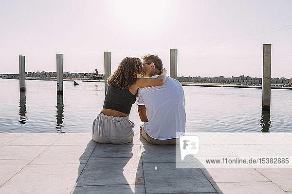 Rückansicht eines jungen Paares  das auf einer Mole am Meer sitzt und sich küsst